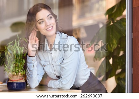 Cafe city lifestyle. Young woman sitting indoor in trendy urban cafe looking through the window. Cool young modern caucasian female model in her 20s - stock photo