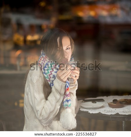 Cafe city woman drinking coffee sitting indoor in trendy cafe. Image is taken through the window - stock photo