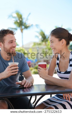 Cafe couple having fun drinking coffee talking smiling and laughing on date in summer. Young man talking with Asian woman sitting outdoors. Happy friends in late 20s. - stock photo