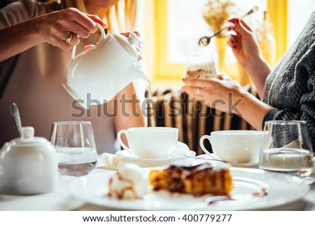 Cafe or bar table with desserts and tea. Two people talking on background. - stock photo