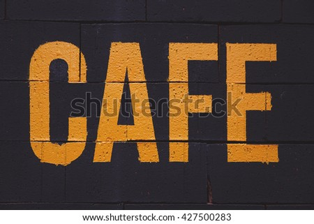 cafe sign painted on a black brick wall - stock photo