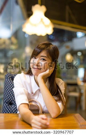 Cafe woman smiling. Asian woman eating at coffee shop. Pensive cheerful young female model. - stock photo