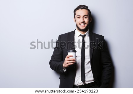 Caffeine for charging before working. Portrait of confident young man in formalwear looking at camera and holding cup of coffee while standing against grey background - stock photo
