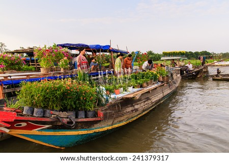 CAI BE TOWN, TIEN GIANG PROVINCE, VIETNAM - FEB 02, 2013: Flower vendors on their boats at Cai Be Floating Market in early morning. Cai Be Market is one of most famous floating market in Vietnam. - stock photo