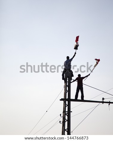 "CAIRO, EGYPT - JULY 1: Two young Egyptians protesting on top of tramway pole holding Egyptian flag near El-Etehadeya palace during ""June 30"" protests against Mohamed Morsy. CAIRO - July 1, 2013 - stock photo"