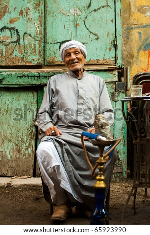 Cairo, Egypt - October 11, 2010: Friendly old Egyptian man wearing a long gray robe, a jellabiya, sitting, laughing at graffiti wall outdoor street cafe smoking sheesha water pipe in Islamic Cairo - stock photo