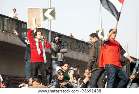 CAIRO – JAN 25: A group of Egyptian protesters on a moving vehicle calling for further political reforms during first anniversary of Egypt's uprising in Tahrir Square in Cairo, Egypt on January 25, 2012 - stock photo