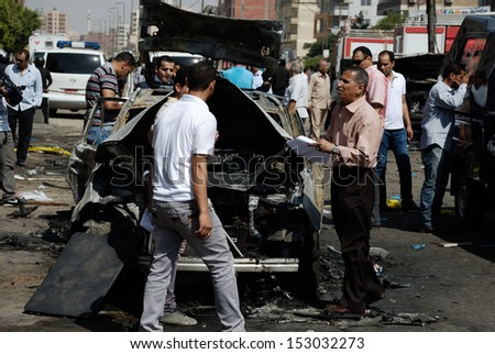 CAIRO - SEP 05: Members of CID search for evidences in an exploded car belongs to interior minister convoy after the explosion of a bomb was targeting the Minister. Cairo, Egypt on September 05, 2013 - stock photo
