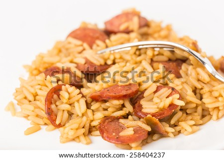 Cajun Dirty Rice with slices of spicy sausage against white background.  Selective focus and shallow of depth of field macro photograph. - stock photo