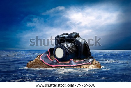 Cake from chocolate photocamera on the island in sea. - stock photo