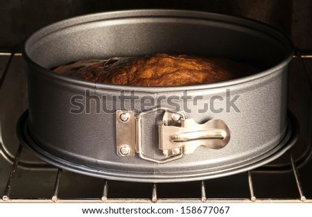 Cake in pan baking in oven - stock photo