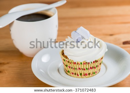 cake on a saucer with a coffee on a wooden background (shallow DOF) - stock photo