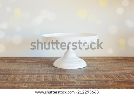 Cake plate on vintage wooden table over bokeh background - stock photo