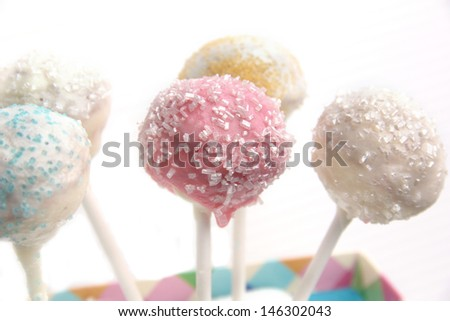 Cake pop treats with pastel icing and sugar sprinkles. - stock photo