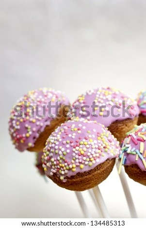 Cake pops - a form of cake styled as a lollipop, invented in USA. Typical dessert of american parties, lavishly embellished. Silver background, copy space. - stock photo