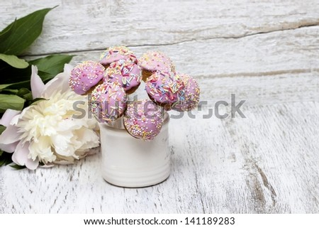 Cake pops and peony flower isolated on white background. Copy space - stock photo