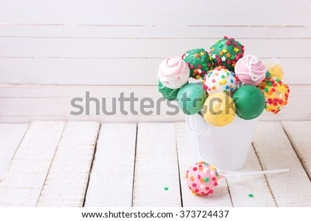 Cake pops in bucket  on white  painted wooden background. Selective focus.Place for text. - stock photo