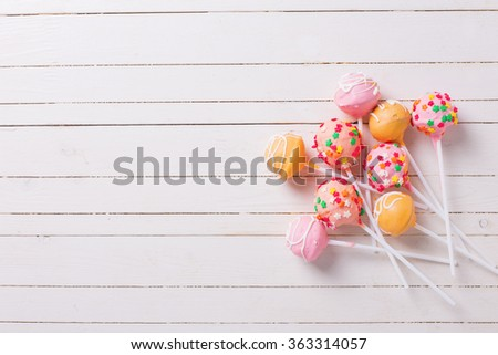 Cake pops on white  painted wooden background. Selective focus.Place for text. - stock photo