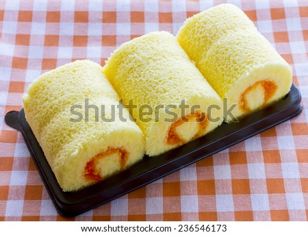 cake roll, swiss roll, Slices of sweet cream roll, Orange roll cake on black pack plate with tartan table cloth - stock photo