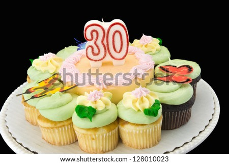 cake surrounded with chocolate and white cupcakes. Butterfly decorations on top of the pastel colored butter cream icing. Unlit number 30 candle adorns the top. - stock photo