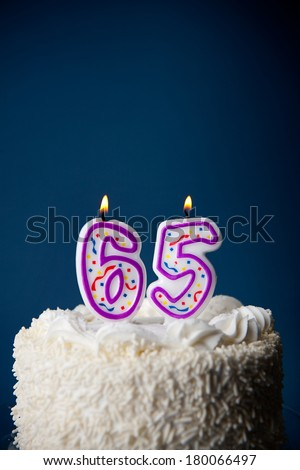 Cake: White Iced Birthday Cake With Candles For 65th Birthday - stock photo