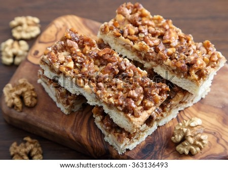 Cake with caramelized walnuts on the wooden background. - stock photo