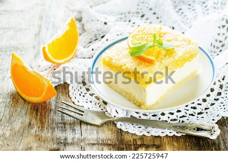 cake with orange, cream cheese and crumbs on a dark woody background. tinting. selective focus on mint - stock photo
