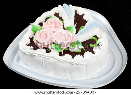 Cake with roses in heart shape on black background. - stock photo