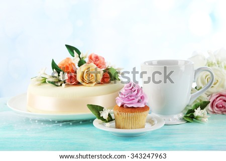 Cake with sugar paste flowers and cupcake, on light background - stock photo