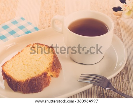 Cake with tea on plate, retro effect - stock photo