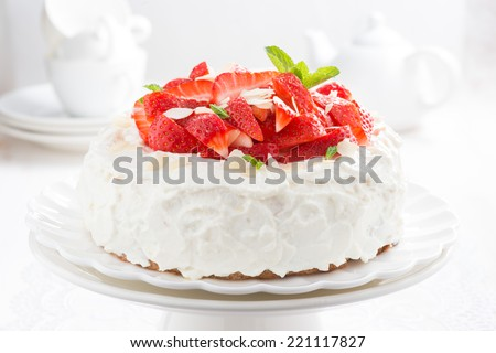 cake with whipped cream and strawberries on a stand, tea accessories in the background, close-up, horizontal - stock photo