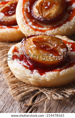 Cakes of flaky pastry with plums close up on an old table. vertical  - stock photo