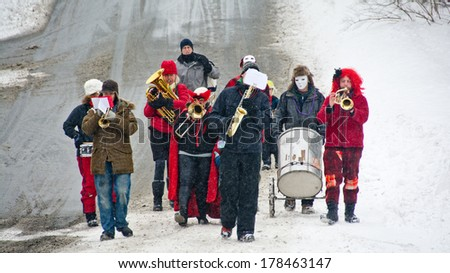 Calais, Vermont, USA - February 15, 2014:  The Plainfield Brass Band marches down County Road at the start of the annual Mardi Gras parade in the village of Maple Corner. - stock photo