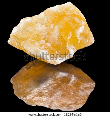 Calcite crystal mineral with reflection on black surface background  - stock photo