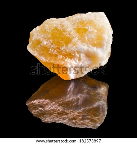 Calcite crystal with reflection on black surface background  - stock photo