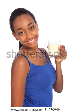 Calcium intake for beautiful young african american girl wearing royal blue vest with happy smile, about to drink a glass of healthy milk. - stock photo
