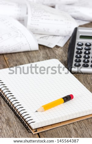 Calculating expenses. Spiral notebook, calculator and grocery shopping receipts - stock photo