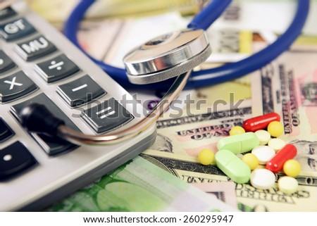 calculator, a stethoscope and medicines on the banknotes, a medical concept - stock photo