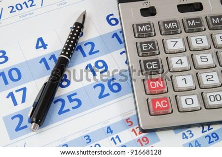 Calculator and black pen on calendar - stock photo