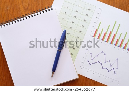 calculator and chart on the wooden table  - stock photo