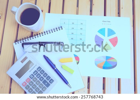calculator and chart on the wooden table with retro effect  - stock photo