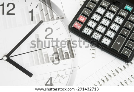 Calculator and clock on financial documents  - stock photo