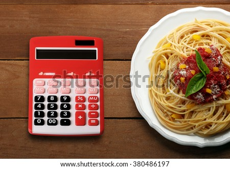 Calculator and delicious spaghetti with tomato sauce on wooden background - stock photo