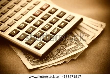 Calculator and dollars. Sepia image. - stock photo
