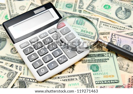 Calculator and magnifier on banknotes (dollars). - stock photo