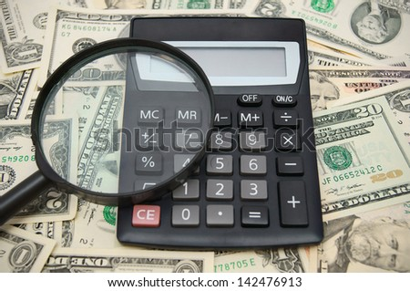 Calculator and magnifier on dollars. - stock photo