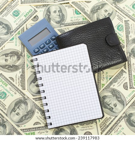 Calculator and notebook on a dollars background - stock photo
