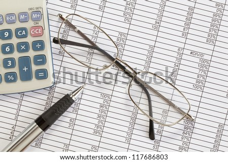 Calculator and pen on  spreadsheets - with glasses - stock photo
