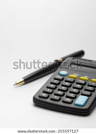 calculator and pen on the white background - stock photo