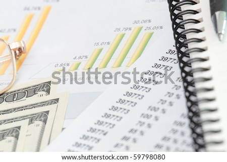 Calculator and pen with dollars, eyeglass and spiral notebook - stock photo
